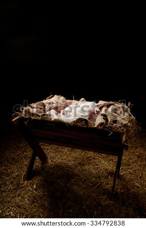 Baby Jesus in the manger with a dark background - stock photo