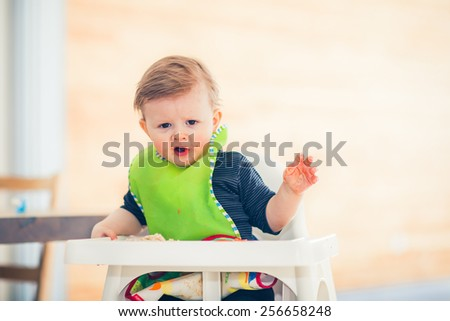 baby kid child boy is eating and the food is all over his face and hand - stock photo