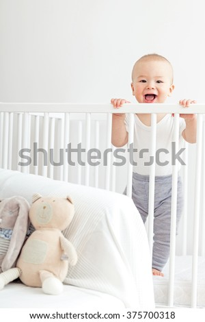 Baby laughing in his crib. - stock photo