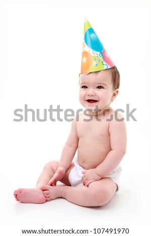 Baby laughing wearing party hat - stock photo