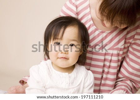 Baby Laughing While Being Embraced By Mother - stock photo
