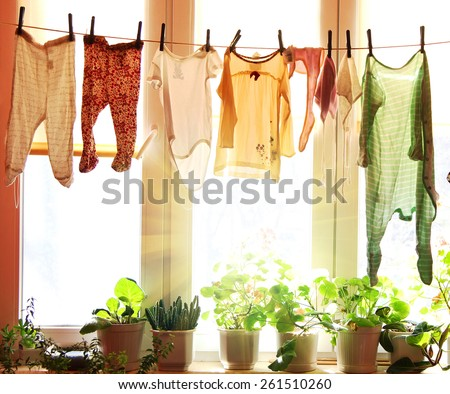 Baby laundry hanging on a clothesline with sun rising on a background - stock photo
