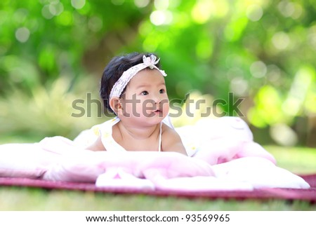 Baby laying in the garden - stock photo