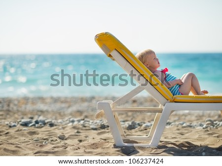 Baby laying on sunbed on beach