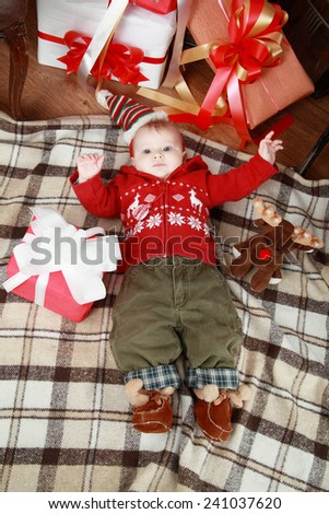Baby laying on the blanket near x-mas gifts - stock photo