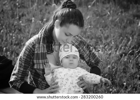 baby learning to walk with  mother - stock photo
