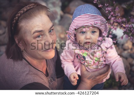 Baby learns the beauty of the world with his grandmother. Together they are looking at a blossoming sakura tree - stock photo
