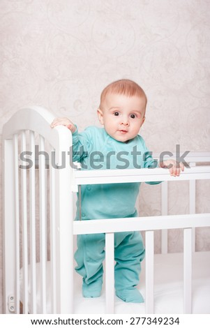 baby learns to stand on his feet . friendly and oboyatelny baby - stock photo