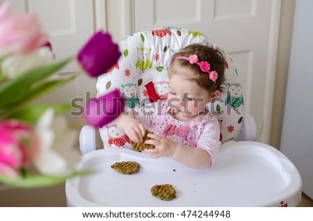 baby led weaning girl eating grilled chicken meatballs for lunch