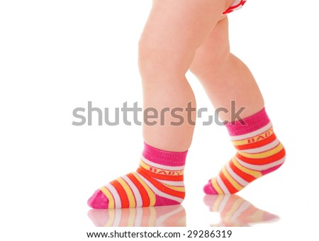 Baby legs in colorful socks walking on glass surface