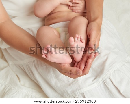 baby legs in mother hands on white background - stock photo