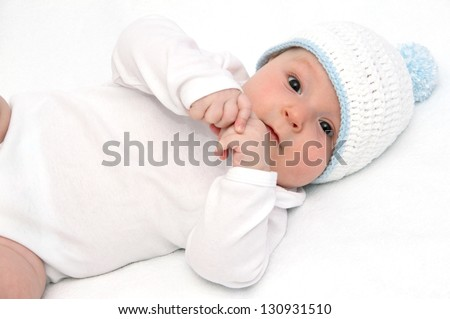 Baby lies on back on white bed - stock photo