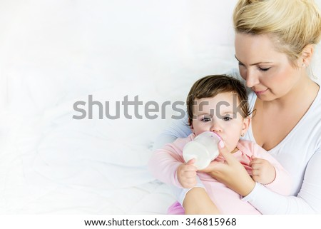 Baby little girl drinking a milk from bottle in the mom's arms.sleeping baby.Shallow doff, copy space - stock photo