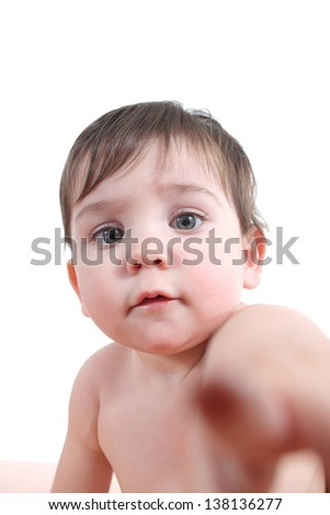 Baby looking and pointing at the camera isolated on a white background