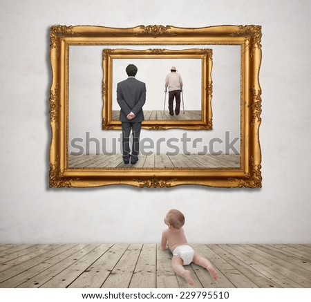 baby looking at a picture of an old man and a young man - stock photo