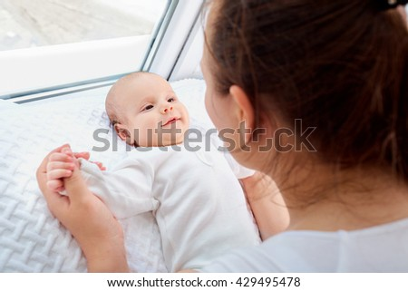 Baby looking at his smiling mother. - stock photo