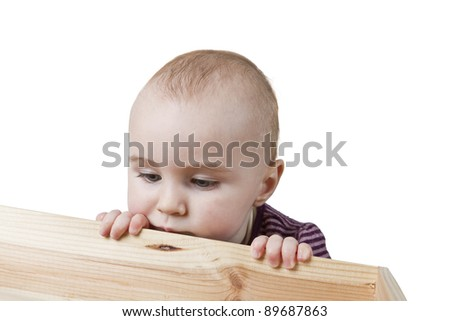 baby looking into wooden box. isolated on white background