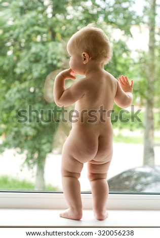 Baby looking out a window - stock photo