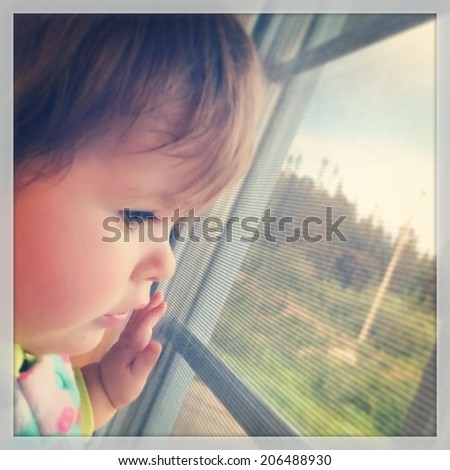 Baby looking out window - With Instagram effect - stock photo