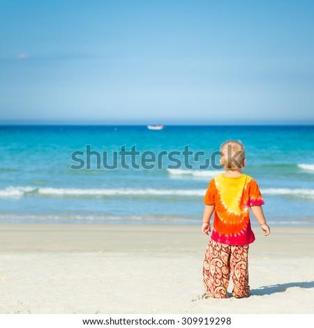Baby looking sea on the beach - stock photo