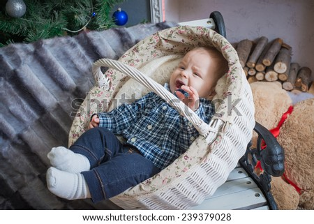 Baby lying in a basket. Christmas tree in the background - stock photo