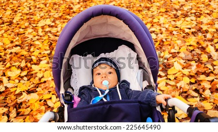 Baby lying in a buggy - stock photo