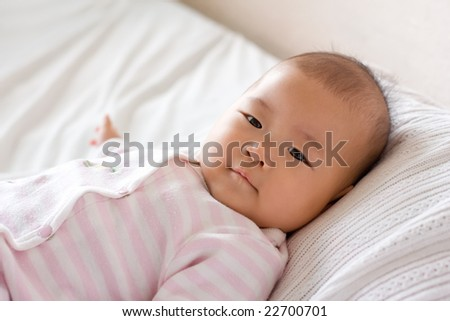 Baby lying in bed, smiling