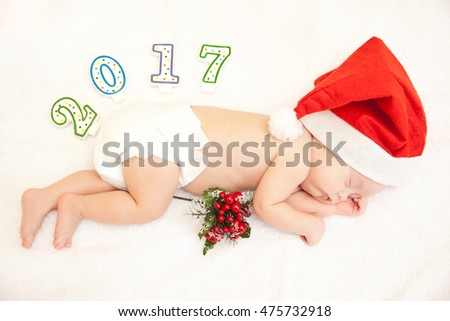 Baby lying in new year hat on white background