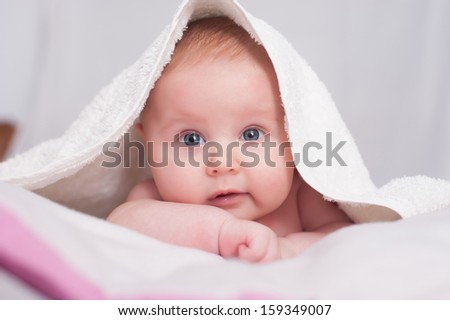 baby lying on a bed under a towel