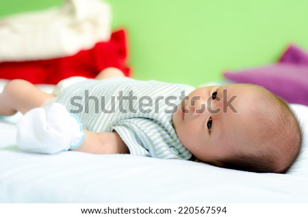 Baby lying on a bed while looking around - stock photo