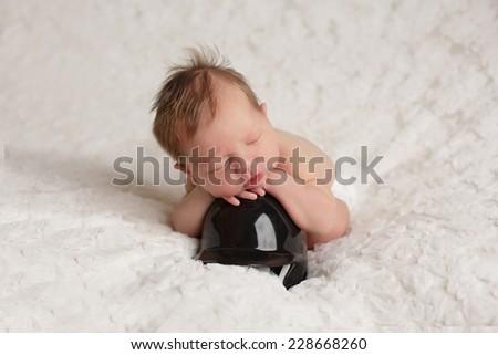 Baby lying on baseball helmet - stock photo