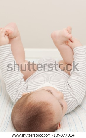 Baby lying on changing table - stock photo