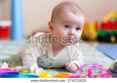 baby lying on floor with kids toys, pained expression on face, surprised expression, frustrated expression - stock photo