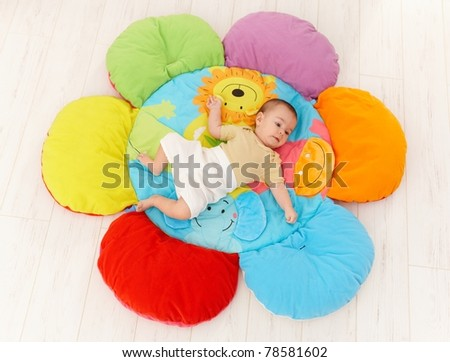 Baby lying on flower shape playmat, high angle.? - stock photo