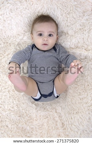 baby lying on his back, playing with his feet - stock photo