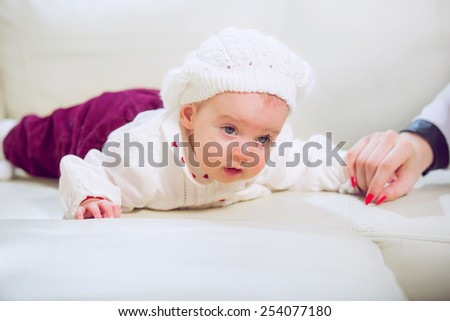 Baby lying on stomach in the living room - stock photo