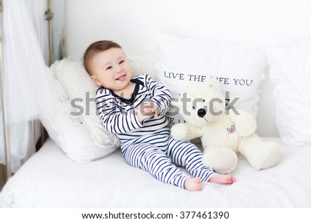 baby lying on the bed with a teddy bear - stock photo