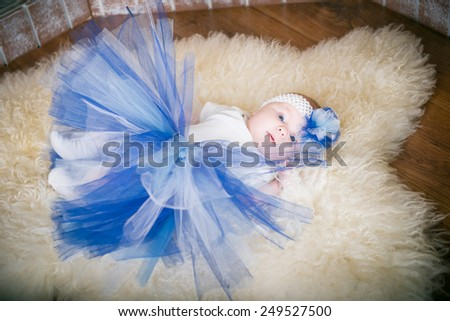 baby lying on the carpet, the little girl in a blue skirt and a blue hat on a white fluffy carpet in the room. The child in the interior - stock photo