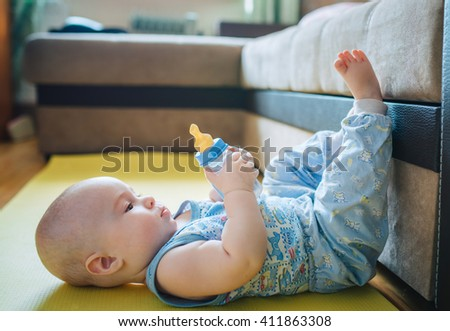 baby lying on the floor with your feet up and holding a bottle of water - stock photo