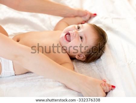 Baby massage. Mother massaging and doing gymnastic to her kid - stock photo