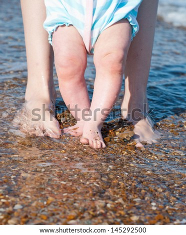 Baby & mother foot on the beach - stock photo