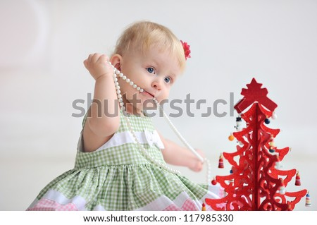 Baby near the red tree. Christmas. Small child playing with beads. Light background. The girl in the dress. - stock photo