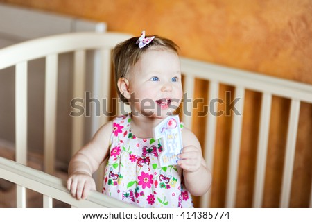 baby newborn girl in orange and beige colors in bed smiling and surprised in body  on birthday - stock photo