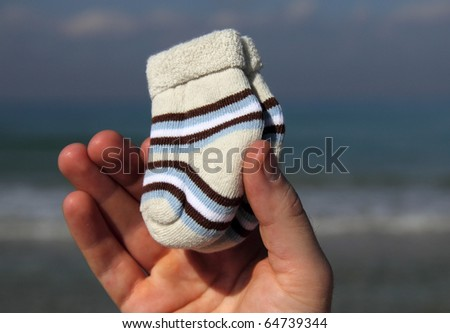 baby newborn socks in men's hands - stock photo