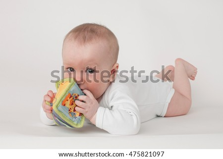 baby on a white background in a white pajamas with toy cube
