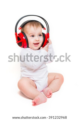 Baby on a white background with headphones listening to music - stock photo