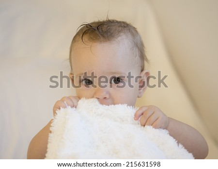 baby on cream background holding fluffy white blanket or towel - stock photo