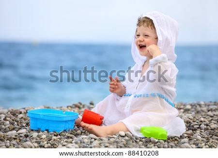 Baby on the beach in white dress