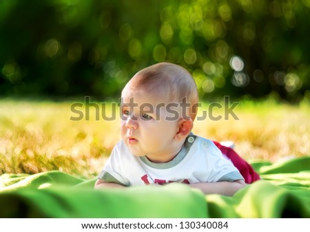 baby on the grass in the spring park - stock photo