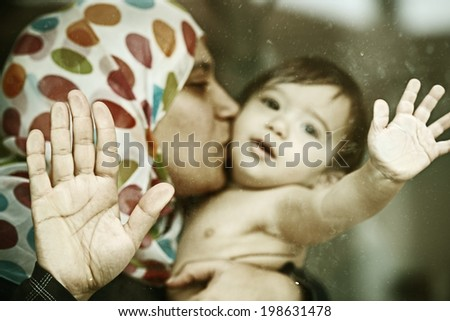 Baby on window glass with mother - stock photo